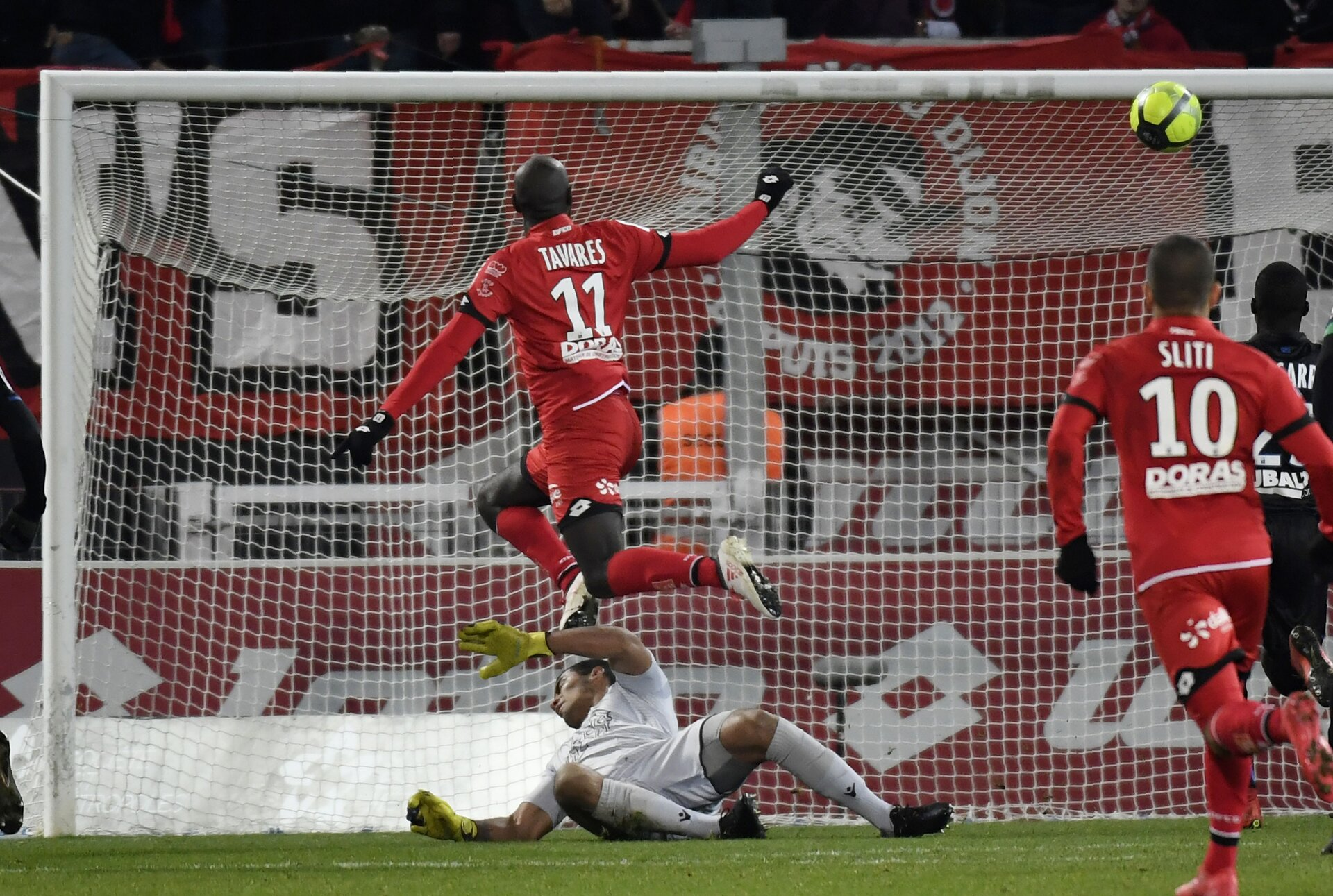 Dijon's Cap Verdean forward Julio Tavares (top) shoots to score a goal during the French L1 football match between Dijon FCO and OGC Nice on February 10, 2018 at the Gaston Gerard stadium in Dijon, central-eastern France.   Dijon's Cap Verde forward Julio Tavares (up) vies with Nice's Argentinian goalkeeper Walter Benitez (down) / AFP PHOTO / PHILIPPE DESMAZES        (Photo credit should read PHILIPPE DESMAZES/AFP/Getty Images)