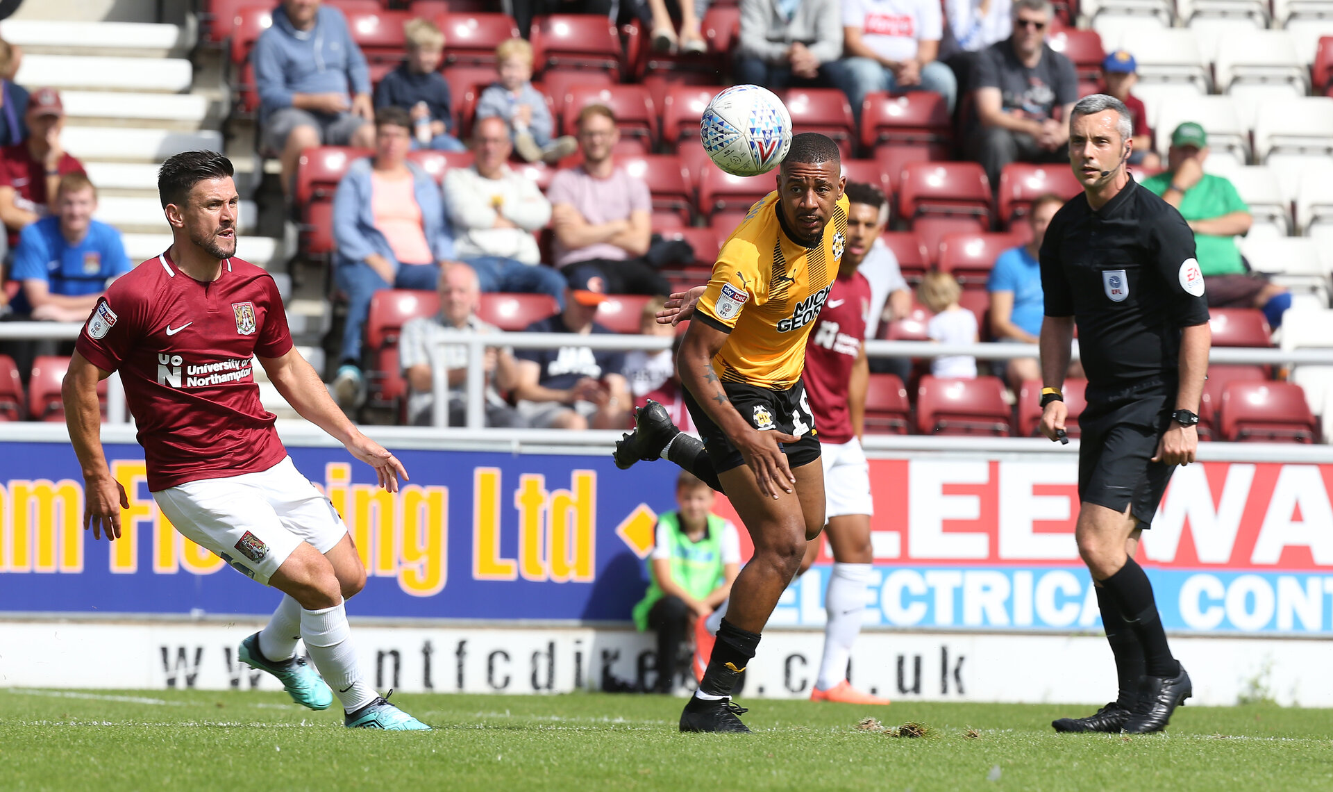 NORTHAMPTON, ENGLAND - AUGUST 18: eggie Lambe of Cambridge United looks to the ball with David Buchanan of Northampton Town and referee Seb Stockbridge during the Sky Bet League Two match between Northampton Town and Cambridge United at PTS Academy Stadium on August 18, 2018 in Northampton, United Kingdom. (Photo by Pete Norton/Getty Images)