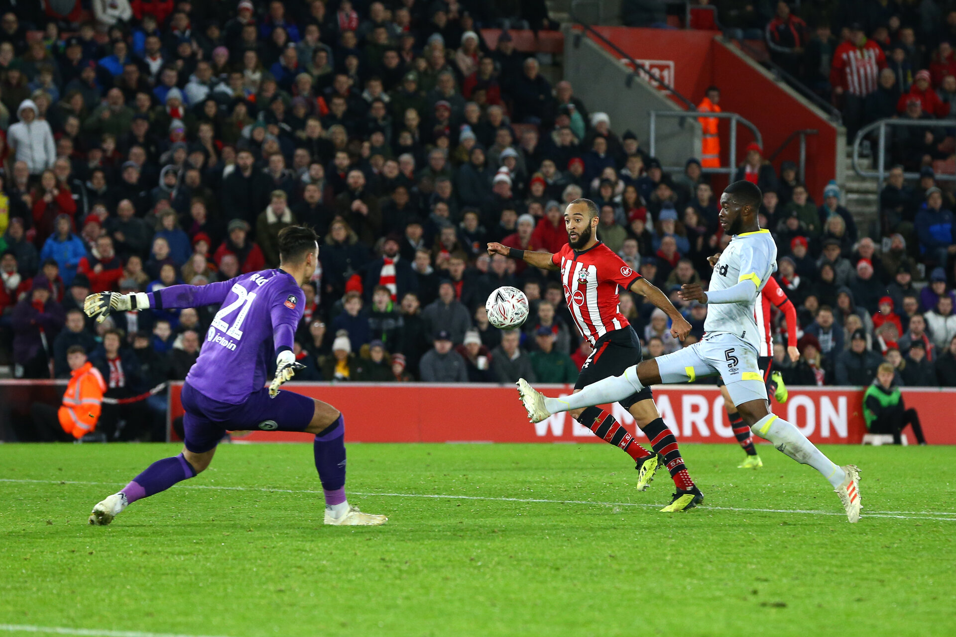 SOUTHAMPTON, ENGLAND - JANUARY 16:  Nathan Redmond (middle) of Southampton FC scores by chipping the ball over Derby County's Kelle Roos (left) during the FA Cup Third Round Replay match between Southampton FC and Derby County at St Mary's Stadium on January 16, 2019 in Southampton, United Kingdom. (Photo by James Bridle - Southampton FC/Southampton FC via Getty Images)