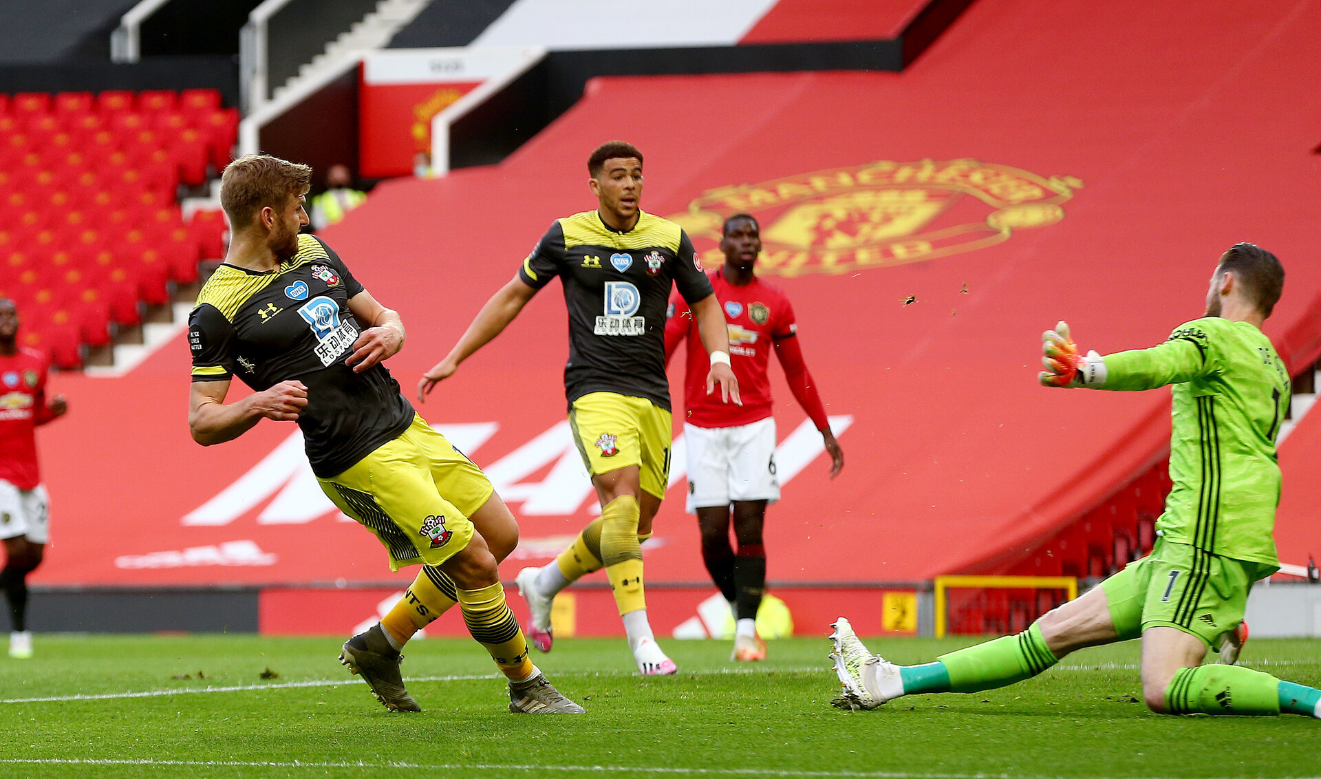 MANCHESTER, ENGLAND - JULY 13: Stuart Armstrong(L) of Southampton scores the opening goal during the Premier League match between Manchester United and Southampton FC at Old Trafford on July 13, 2020 in Manchester, United Kingdom. Football Stadiums around Europe remain empty due to the Coronavirus Pandemic as Government social distancing laws prohibit fans inside venues resulting in all fixtures being played behind closed doors. (Photo by Matt Watson/Southampton FC via Getty Images)