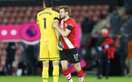 SOUTHAMPTON, ENGLAND - JANUARY 30: Alex McCarthy (L) of Southampton and Stuart Armstrong (R) of Southampton  during the Premier League match between Southampton and Aston Villa at St Mary's Stadium on January 30, 2021 in Southampton, England. Sporting stadiums around the UK remain under strict restrictions due to the Coronavirus Pandemic as Government social distancing laws prohibit fans inside venues resulting in games being played behind closed doors. (Photo by Matt Watson/Southampton FC via Getty Images)
