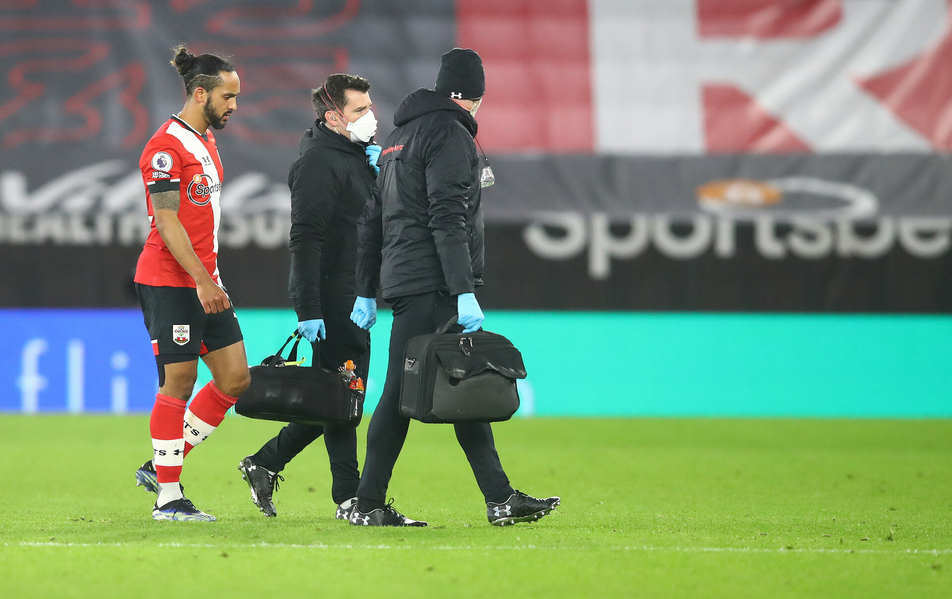SOUTHAMPTON, ENGLAND - JANUARY 30: Theo Walcott(L) of Southampton leaves the pitch with an injury alongside Southampton FC medical staff during the Premier League match between Southampton and Aston Villa at St Mary's Stadium on January 30, 2021 in Southampton, England. Sporting stadiums around the UK remain under strict restrictions due to the Coronavirus Pandemic as Government social distancing laws prohibit fans inside venues resulting in games being played behind closed doors. (Photo by Matt Watson/Southampton FC via Getty Images)