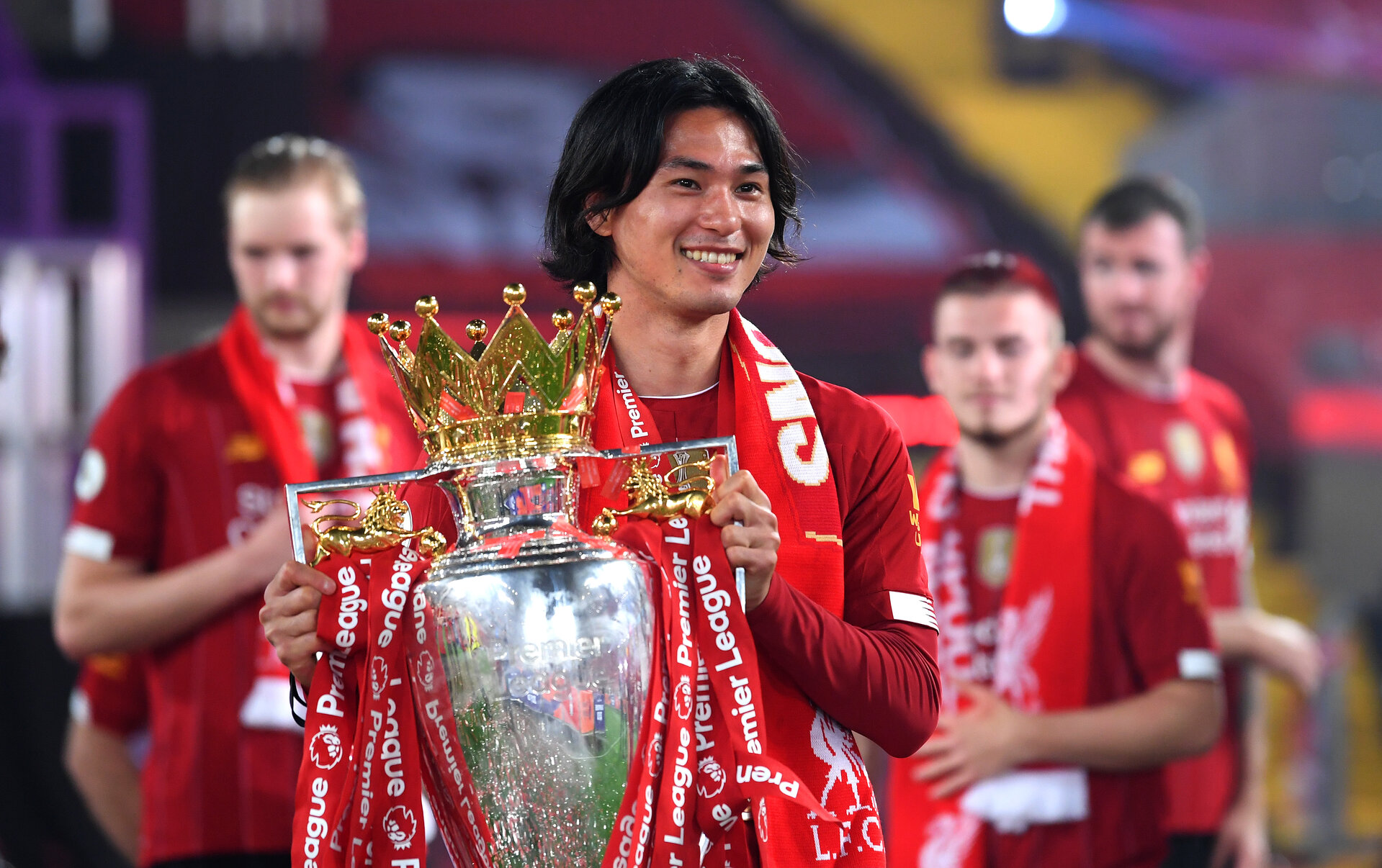 LIVERPOOL, ENGLAND - JULY 22: Takumi Minamino of Liverpool celebrates with The Premier League trophy following the Premier League match between Liverpool FC and Chelsea FC at Anfield on July 22, 2020 in Liverpool, England. Football Stadiums around Europe remain empty due to the Coronavirus Pandemic as Government social distancing laws prohibit fans inside venues resulting in all fixtures being played behind closed doors. (Photo by Laurence Griffiths/Getty Images)