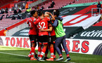 SOUTHAMPTON, ENGLAND - APRIL 04: Nathan Redmond of Southampton is mobbed by his team mates after putting his team 3-2 up during the Premier League match between Southampton and Burnley at St Mary's Stadium on April 04, 2021 in Southampton, England. Sporting stadiums around the UK remain under strict restrictions due to the Coronavirus Pandemic as Government social distancing laws prohibit fans inside venues resulting in games being played behind closed doors. (Photo by Matt Watson/Southampton FC via Getty Images)