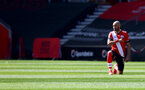 SOUTHAMPTON, ENGLAND - APRIL 04: Nathan Redmond of Southampton takes a knee during the Premier League match between Southampton and Burnley at St Mary's Stadium on April 04, 2021 in Southampton, England. Sporting stadiums around the UK remain under strict restrictions due to the Coronavirus Pandemic as Government social distancing laws prohibit fans inside venues resulting in games being played behind closed doors. (Photo by Matt Watson/Southampton FC via Getty Images)