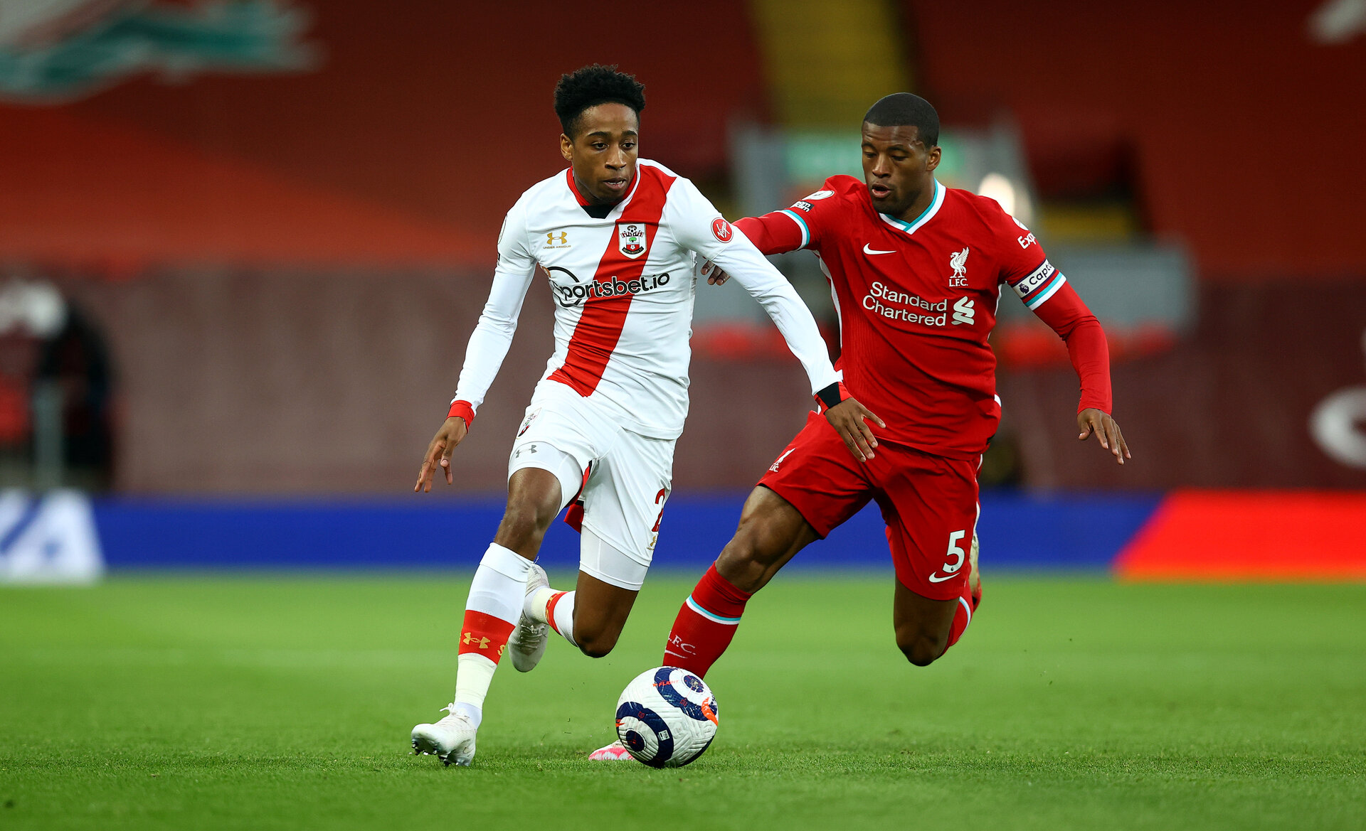 LIVERPOOL, ENGLAND - MAY 08: Kyle Walker-Peters(L) of Southampton and Georginio Wijnaldum(R) of Liverpool during the Premier League match between Liverpool and Southampton at Anfield on May 08, 2021 in Liverpool, England. Sporting stadiums around the UK remain under strict restrictions due to the Coronavirus Pandemic as Government social distancing laws prohibit fans inside venues resulting in games being played behind closed doors. (Photo by Matt Watson/Southampton FC via Getty Images)