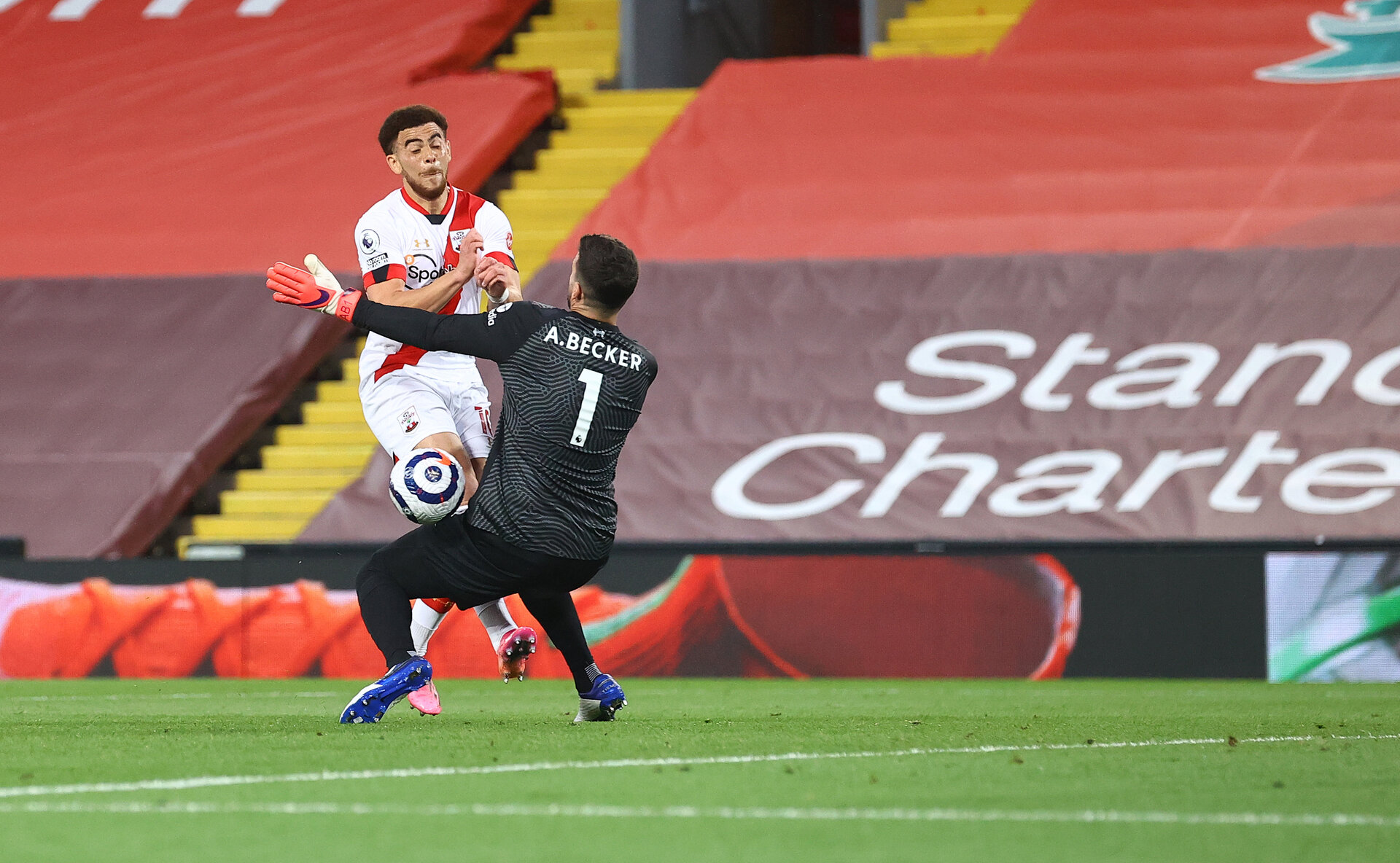 LIVERPOOL, ENGLAND - MAY 08: Che Adams(L) of Southampton is denied by Liverpool goalkeeper Alisson Becker during the Premier League match between Liverpool and Southampton at Anfield on May 08, 2021 in Liverpool, England. Sporting stadiums around the UK remain under strict restrictions due to the Coronavirus Pandemic as Government social distancing laws prohibit fans inside venues resulting in games being played behind closed doors. (Photo by Matt Watson/Southampton FC via Getty Images)