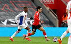 SOUTHAMPTON, ENGLAND - MAY 11: Wilfried Zaha (L) of Crystal Palace and Takumi Minamino (R) of Southampton during the Premier League match between Southampton and Crystal Palace at St Mary's Stadium on May 11, 2021 in Southampton, England. Sporting stadiums around the UK remain under strict restrictions due to the Coronavirus Pandemic as Government social distancing laws prohibit fans inside venues resulting in games being played behind closed doors.  (Photo by Matt Watson/Southampton FC via Getty Images)