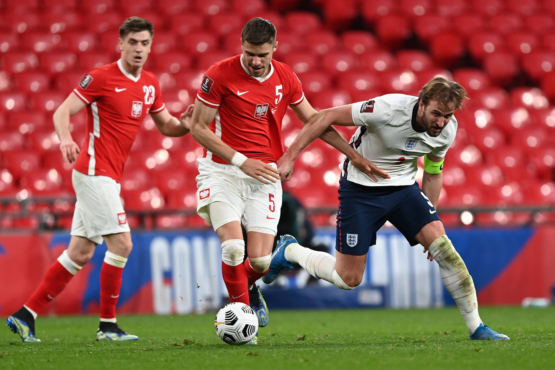 LONDON, ENGLAND - MARCH 31: Harry Kane of England is challenged by Jan Bednarek of Poland during the FIFA World Cup 2022 Qatar qualifying match between England and Poland on March 31, 2021 at Wembley Stadium in London, England. Sporting stadiums around the UK remain under strict restrictions due to the Coronavirus Pandemic as Government social distancing laws prohibit fans inside venues resulting in games being played behind closed doors. (Photo by Andy Rain - Pool/Getty Images)