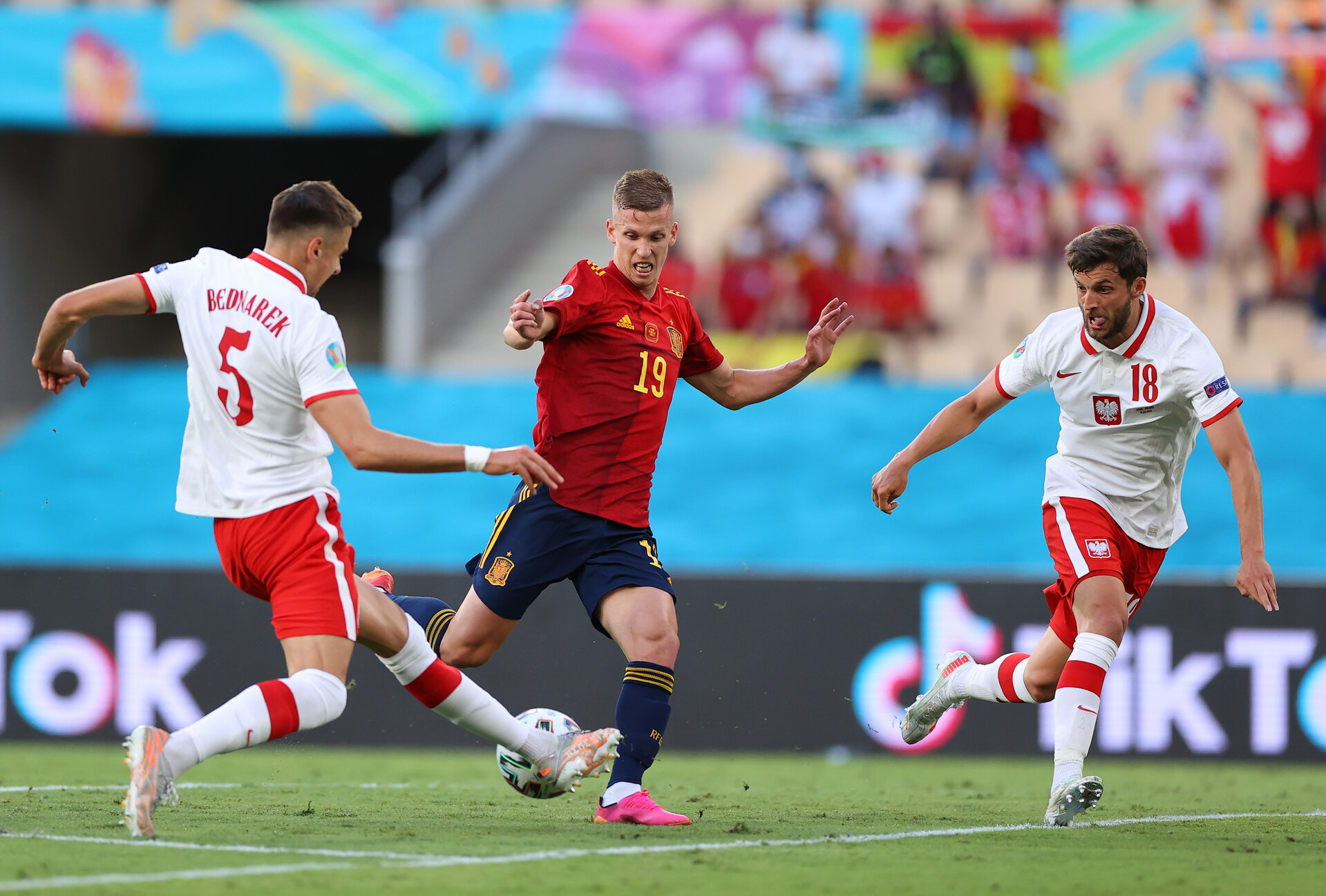 SEVILLE, SPAIN - JUNE 19: Dani Olmo of Spain shoots whilst under pressure from Jan Bednarek and Bartosz Bereszynski of Poland during the UEFA Euro 2020 Championship Group E match between Spain and Poland at Estadio La Cartuja on June 19, 2021 in Seville, Spain. (Photo by Fran Santiago - UEFA/UEFA via Getty Images)
