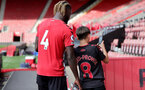 SOUTHAMPTON, ENGLAND - SEPTEMBER 19: Dynel Simeu(L) of Southampton and a young Southampton fan(R) during the Premier League 2 match between Southampton B Team and Burnley at St Mary's Stadium on September 19, 2021 in Southampton, England. (Photo by Isabelle Field/Southampton FC via Getty Images)
